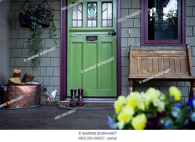 Rubber boots on welcome mat at green painted door