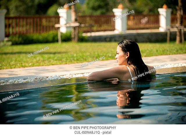 Woman leaning on edge of swimming pool