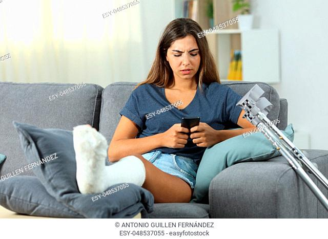 Front view of a disabled girl messaging with a smart phone sitting on a couch at home