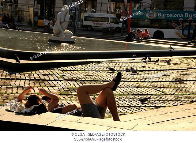 Tourists resting at Plaza Catalunya. Barcelona, Catalonia, Spain