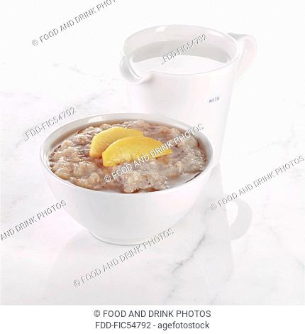 Bowl of Porridge with Sliced Peaches and a Jug of Milk