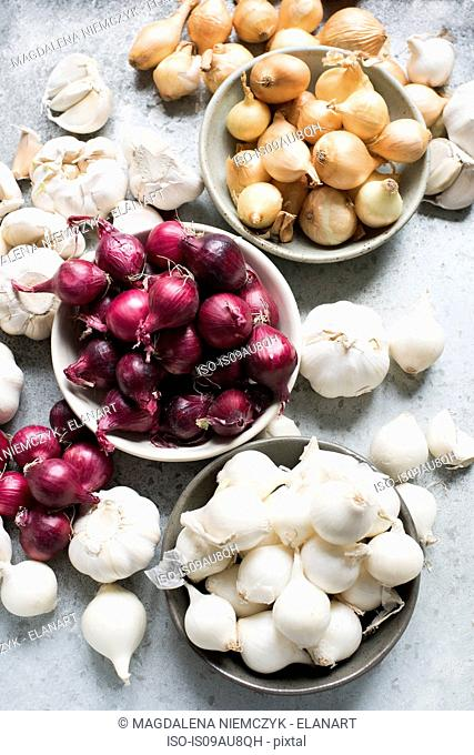 Overhead view of garlic bulbs and onions in bowls