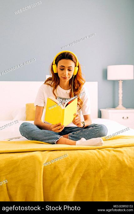 Young woman reading a book and listening to music on bed at home