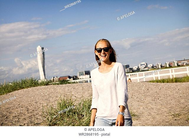 Happy young woman walking at beach against sky