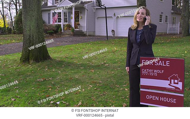 TU, MS, real estate agent standing next to FOR SALE sign, outdoors, on the phone