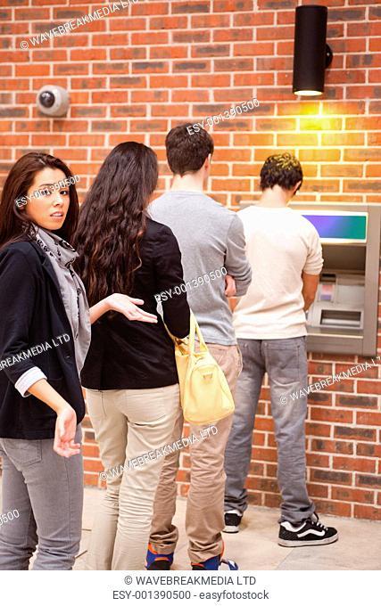 Portrait of an impatient woman queuing at an ATM