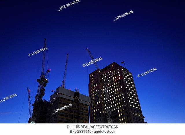 Dos edificios uno en costruccion y otro con luz en todas las ventanas en la City al anochecer.. Londres, West End, UK, Europa