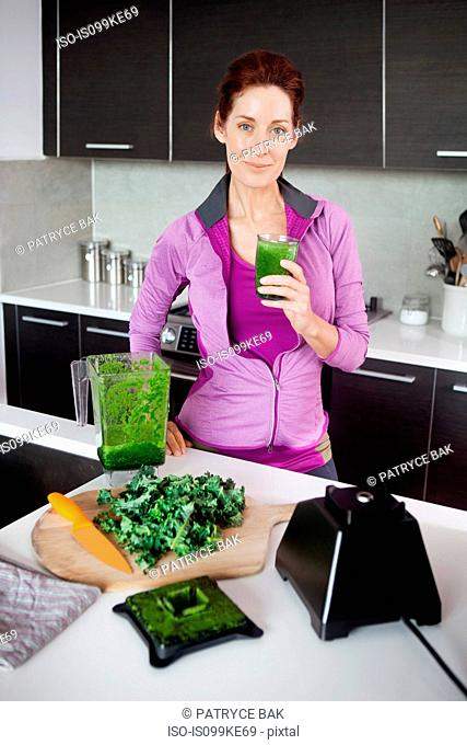 Mature woman with glass of fresh vegetable juice