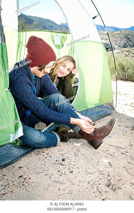 Young couple sitting in tent, young man putting on boots