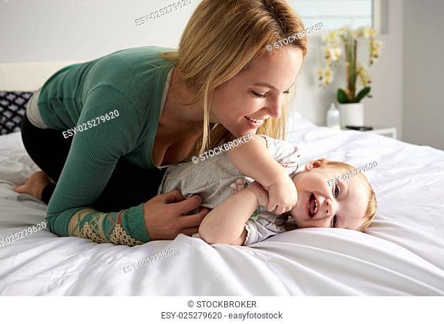Caucasian mother kneeling on bed, tickling her baby daughter