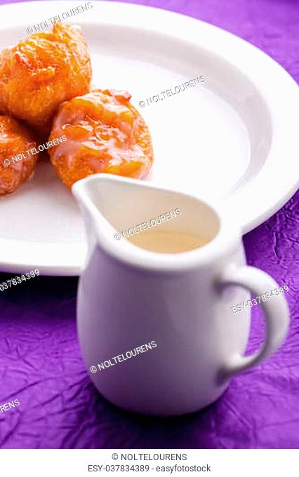 A big plate of freshly made saucy and golden pumpkin fritters