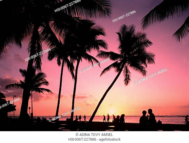 Thailand. Phuket Island. Sunset over waterfront with people and palm trees silhouetted