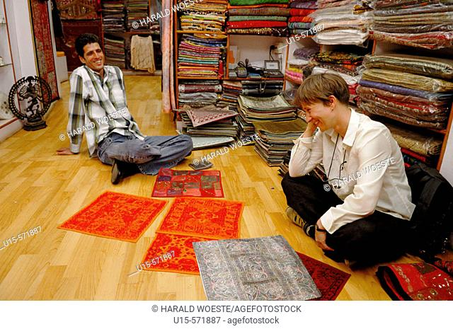 German female tourist negotiating prices for typical indian fabrics in a small boutique in the jewish part of Cochin (Kochi)
