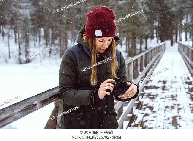 Young woman with camera in winter