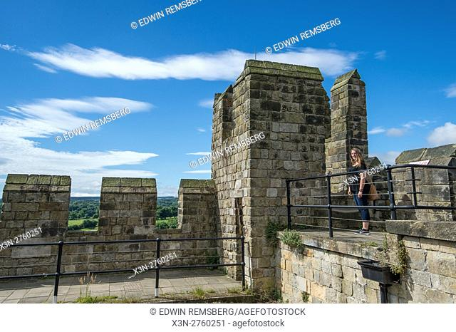 UK, England, Yorkshire, Richmond - A young female tourist posing at the top of the Richmond Castle, one of North Yorkshire's most popular tourist attractions...