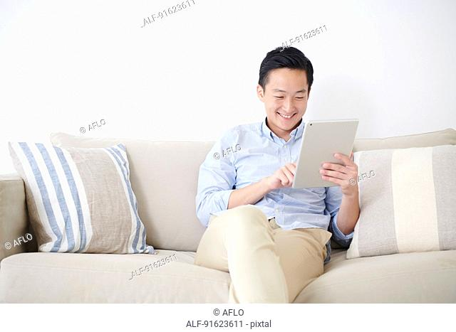 Young Japanese man using tablet on the sofa