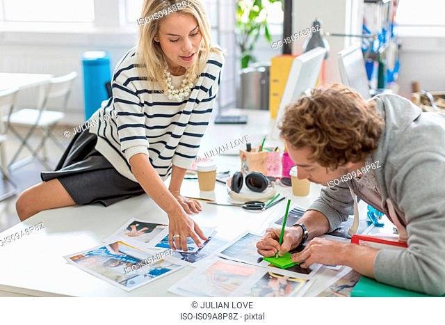 Young colleagues discussing photographs in meeting in creative office