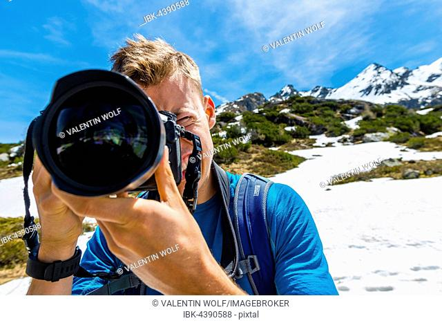 Young man photographing, Rohrmoos-Untertal, Schladming Tauern, Schladming, Styria, Austria