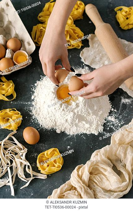 Hands of woman cracking egg onto flour