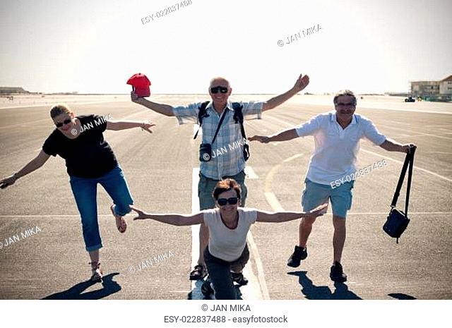 Funny people imitating airplane at airport runway