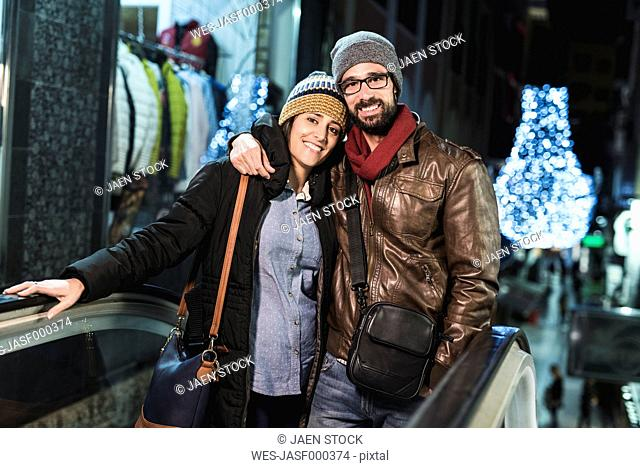 Couple on escalator with shops and night lights in background