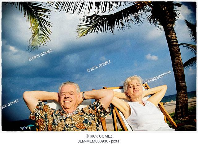 Older couple relaxing on tropical beach