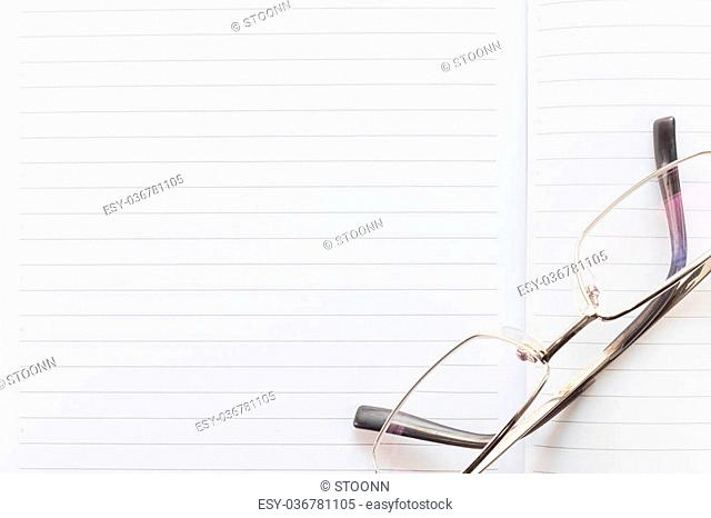 Notebook open blank page and Eyeglasses on wood table