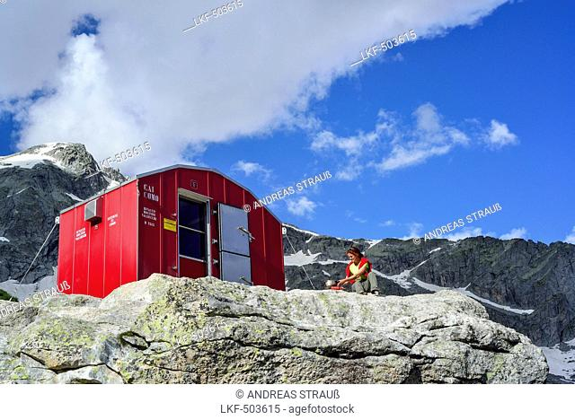 Woman sitting in front of red bivouac with granite mountains in background, bivouac Molteni, Sentiero Roma, Bergell range, Lombardy, Italy