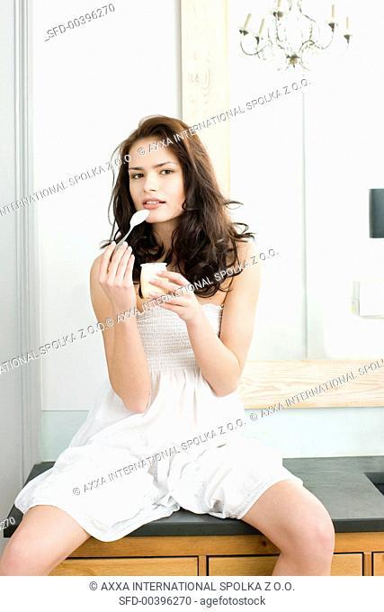 Young woman eating yoghurt
