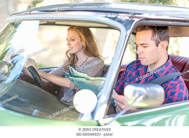 Heterosexual couple in car together, looking lost