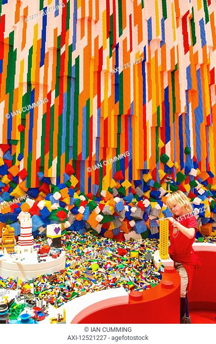 Boy building Lego tower in the Red Zone of the Lego House; Billund, Denmark