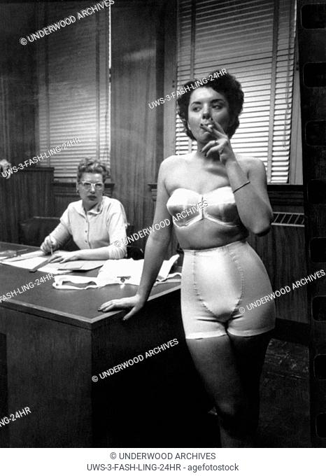 Chicago, Illinois: 1949 A fashion model wearing a strapless bra and girdle, standing in an office smoking