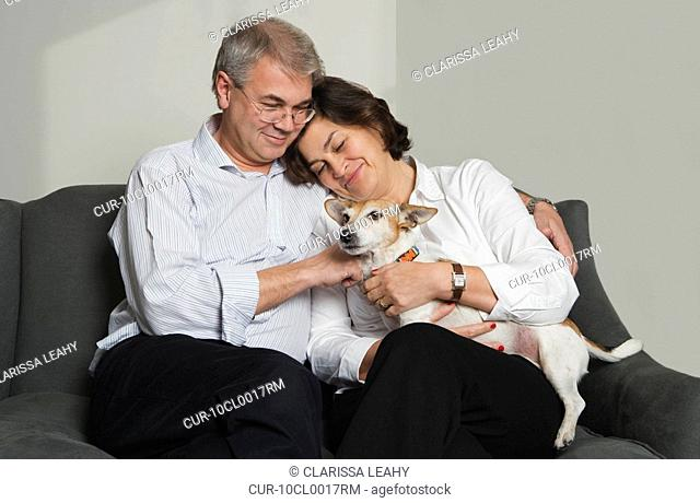 Mature couple playing with dog on sofa