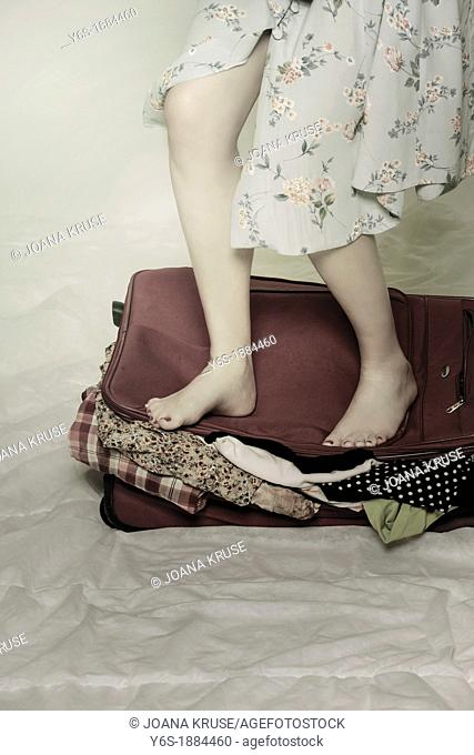 a woman tries to close a suitcase with her feet