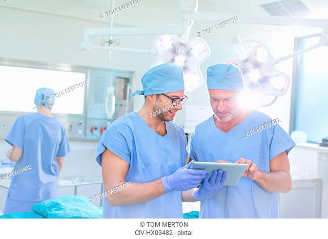 Male surgeons talking, using digital tablet in operating room