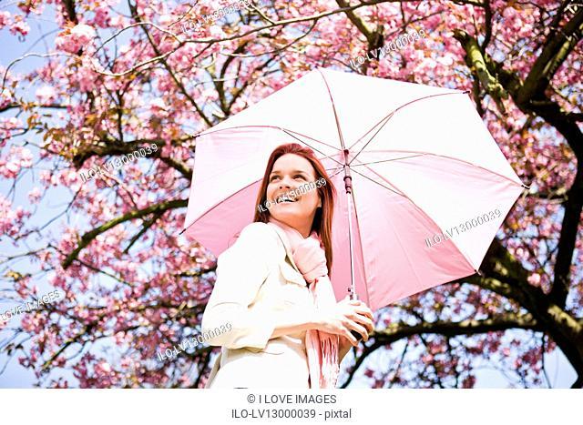 A young woman holding an umbrella, in springtime