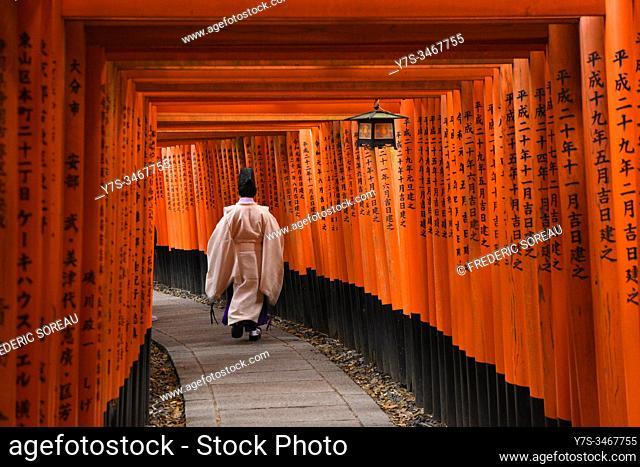Japanese Priest walking up hill in Kyoto most famous shrine, Fushimi Inari shrine, Honshu, Japan, Asia