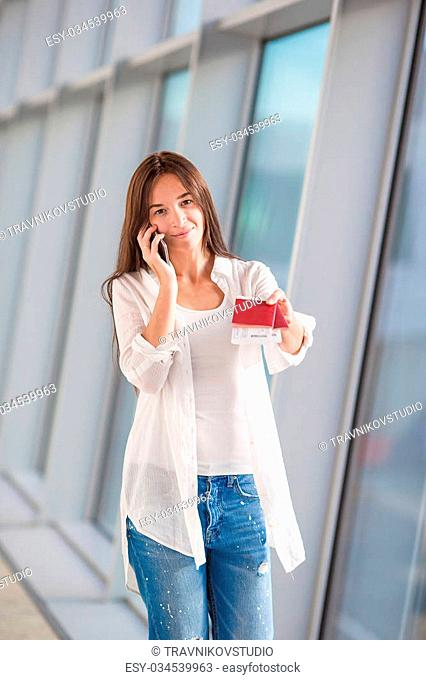Woman talking by cell phone with boarding passport at airport