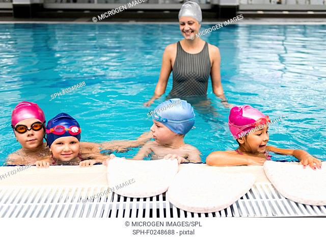 Group of children in a swimming class, instructor in the back