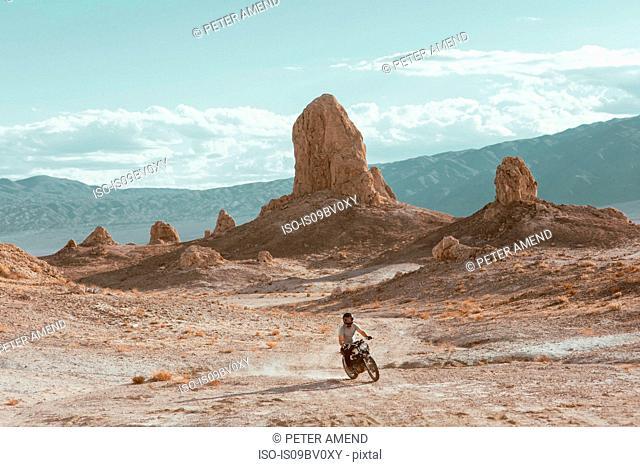 Motorcyclist riding in desert, Trona Pinnacles, California, US