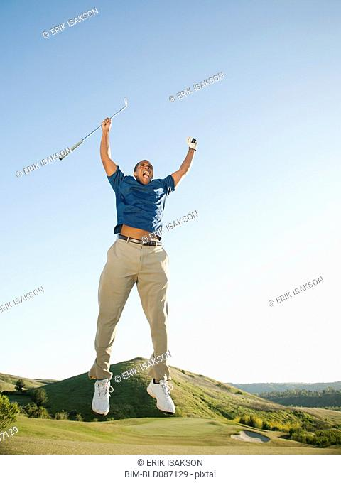 Excited Black golfer jumping in mid-air on golf course