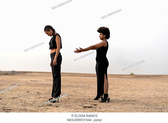 Two women dressed in black standing in bleak landscape