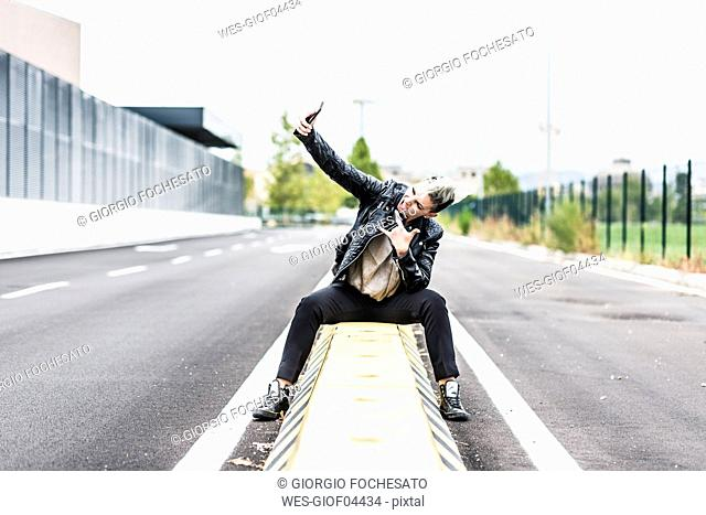 Punk woman sitting at the roadside posing for a selfie