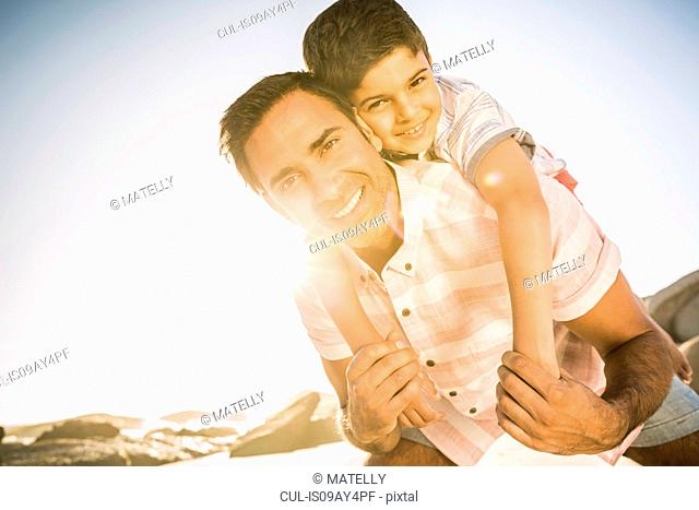 Father giving son piggyback ride on beach