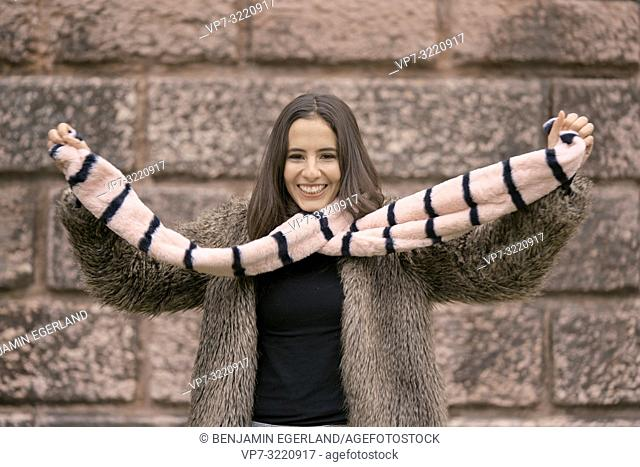 fashionable woman playing with scarf, happy laughing, in Munich, Germany