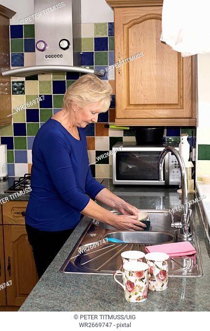 Elderly woman washing up at the kitchen sink