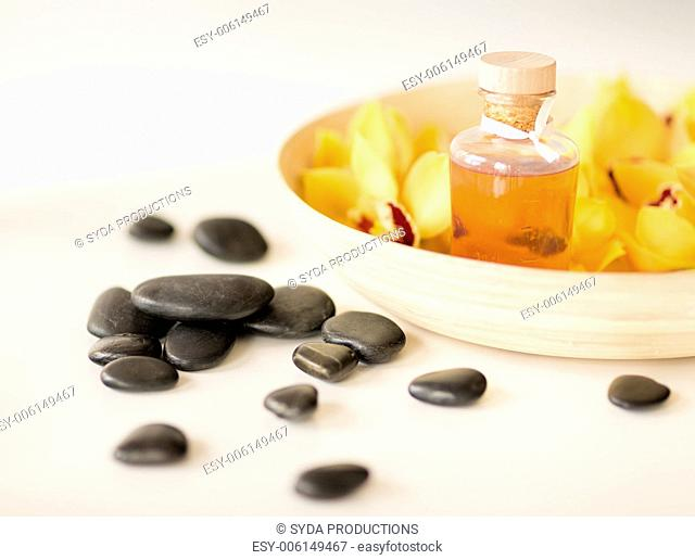spa, heath and beauty concept - massage stones with orchid flowers on table