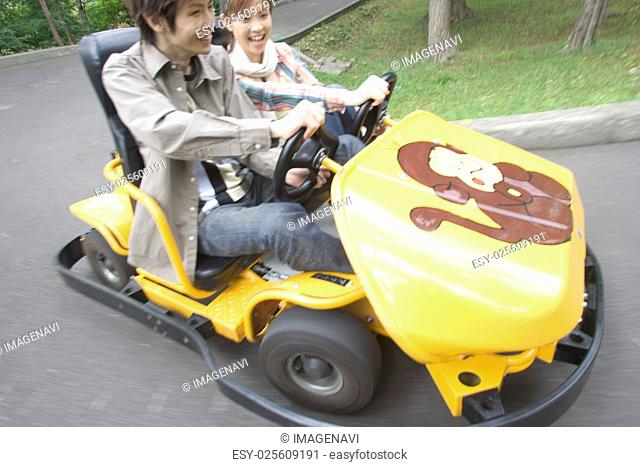 Young couple riding in a go-cart