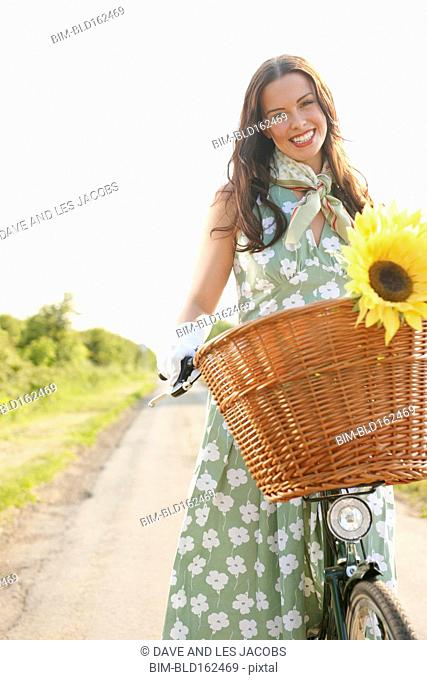 Caucasian woman riding bicycle with basket of flowers