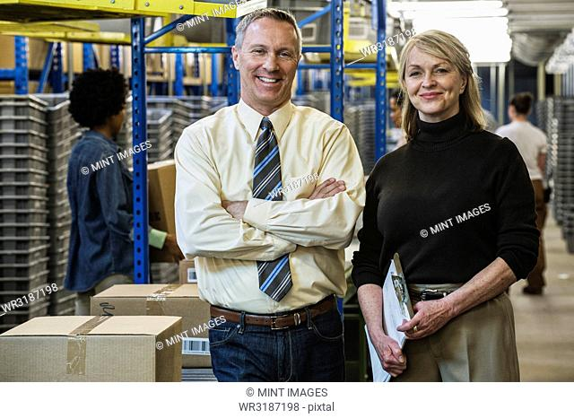 Portrait of a Caucasian male executive in a shirt and tie and a Caucasian female executive in sweater and slacks standing next to a motorized conveyor system in...